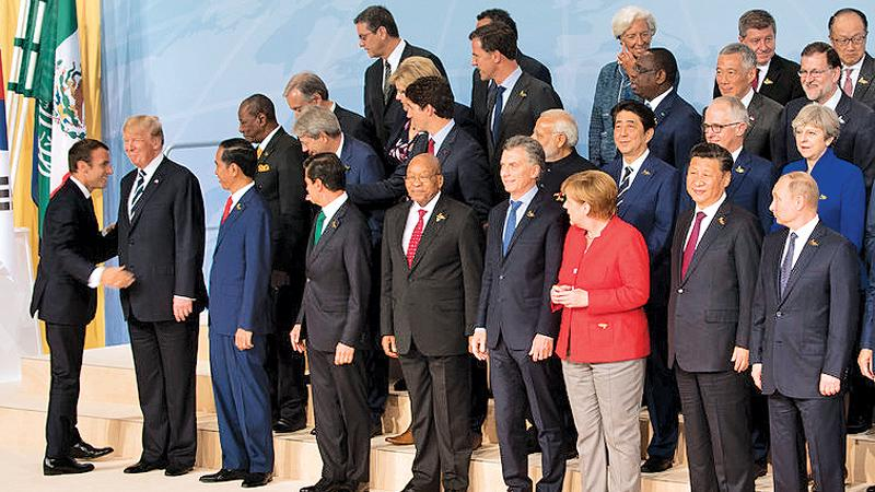 G-20 leaders posed in Hamburg, Germany, on Friday. President Emmanuel Macron of France was with President Trump at left.   Pic: The New York Times