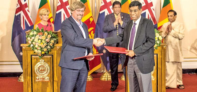 Director of the Eliminate Dengue Program Scott O'Neill and Secretary, Ministry of Health, Nutrition and Indigenous Medicine, Janaka Sugathadasa exchange notes of intent for a research partnership to seek a long-term solution to the dengue burden in Sri Lanka at the Foreign Ministry. Australian Foreign Minister Julie Bishop, Foreign Minister Ravi Karunanayake and Health Minister Dr Rajitha Senaratne look on.