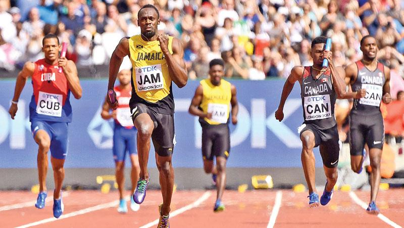 Jamaica's Usain Bolt (C) races to the finish line on the anchor leg ahead to win their heat in the men's 4x100m relay .
