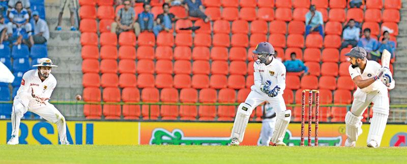 Indian captain Virat Kohli is caught by Sri Lanka slip fielder Dimuth Karunaratne off Lakshan Sandakan (not in picture) for 42 on the opening day of the third and final cricket Test at the Pallakele International Stadium yesterday.  (Pix by RUKMAL GAMAGE)