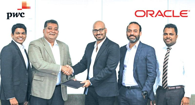 Partner/Advisory Leader PwC Sri Lanka and Maldives, Channa Manoharan exchanges the agreement with  Regional Director South Asia Growth Economies, Oracle Cloud, Chanditha Samaranayake. Officials of PwC and Oracle Cloud look on.