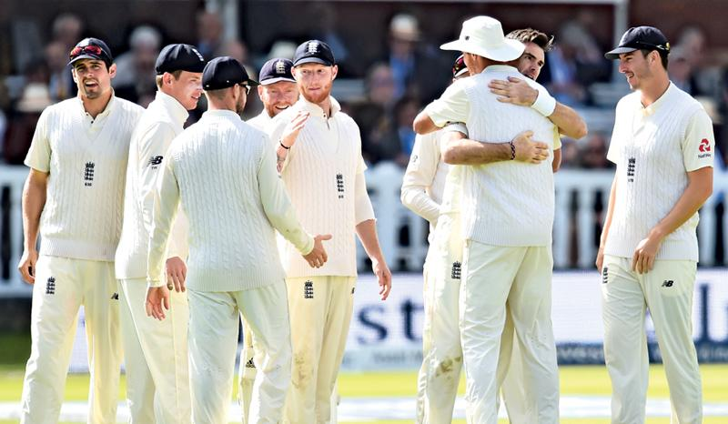 England's James Anderson (2R) celebrates with teammates after taking the wicket of West Indies' Shai Hope during the third day of the third international Test match between England and West Indies at Lord's cricket ground in London. - AFP