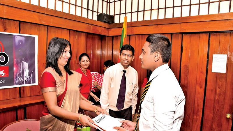 Dr. Malika Weerasinghe handing over  a certificate to a schoolboy