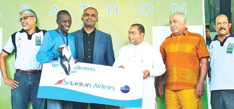 Full Marathon winner James Tallam receives the award fromWestern Province Chief Minster  Isuru Devapriya. Also in the picture are from left chief Executive Offcer SriLankan Airlines, Suren Ratwatte, Acting Sports Minister M.H.M. Haris, Chairman Tourist Promotion Board Udaya  Nanayakkara and Chief organizer LSR Colombo Marathon and Chairman Sports  Rieson Lanka Ltd. Thilak Weerasinghe