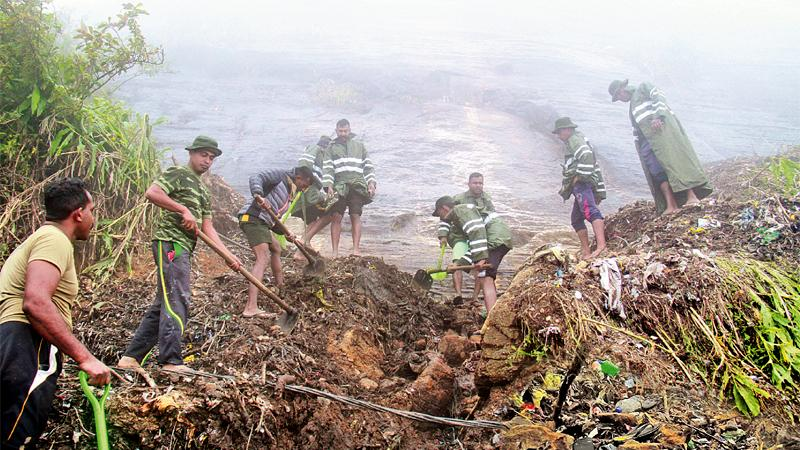 Sri Lanka Army's 3rd Battalion of the Sinha Regiment and the Sri Lanka, National Guard were left to deal with clearing up the garbage and the debris.  (Pix: Ranga Udugama)