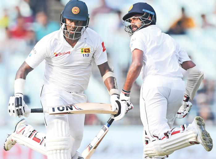 Sri Lanka's Angelo Mathews (L) and Lahiru Thirimanne run between the wickets during the third day of the first Test between India and Sri Lanka at the Eden Gardens cricket stadium in Kolkata. - AFP