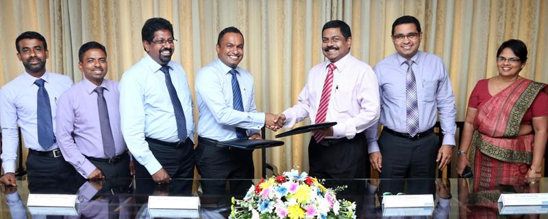 Commercial Bank's Executive Director/Chief Operating Officer S. Renganathan (third from right) and Hayleys Agriculture Director Lushan Nalinda Abeysekara exchange the agreement. Senior representatives of the two companies look on.