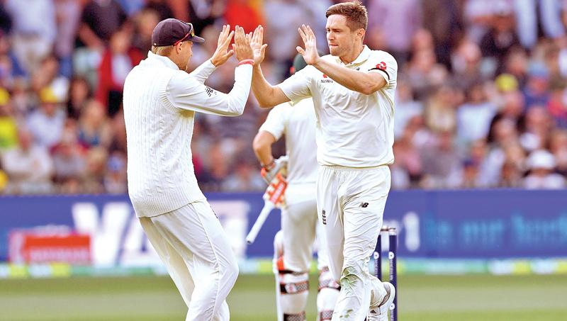 England bowler Chris Woakes (R) celebrates with captain Joe Root (L) after dismissing Australian batsman David Warner.- AFP
