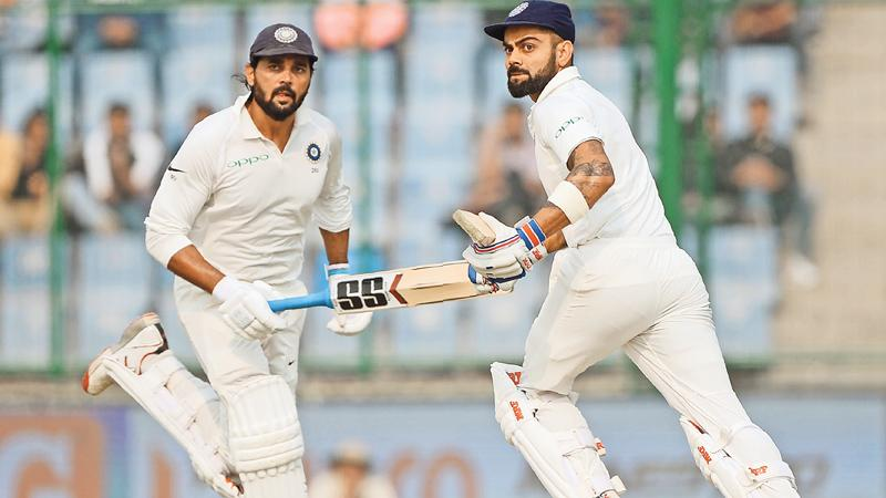 Indian captain Virat Kohli and opening bat Murali Vijay who hit a century apiece and figured in a ---century stand partnership for the third wicket running between the wickets on the first day of the third and final cricket Test against Sri Lanka at the Feroz Shah Kotla Stadium in Delhi on Saturday.  AFP