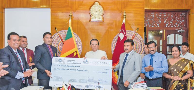 President Maithripala Sirisena handing over the cheque to Dinesh Priyantha.