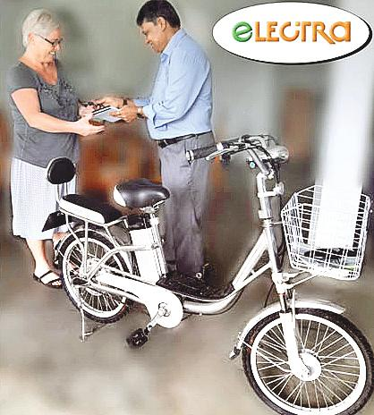 Managing Director, Eco Trans Lanka Holdings, Chrysantha Fernando presents  the keys to a customer who purchased an electric motorcycle.