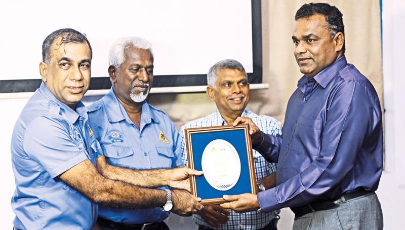 Ashhar Hameem hands over the memento to Base Commander of the Katukurunda Base Mohan Balasooriya. Also in the picture are Andrew Silva Secretary SMSC and Lion Wasantha Weerasekera.