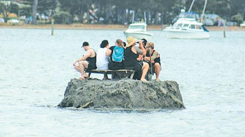 The New Year revellers enjoyed a drink on the sand island they built in an apparent attempt to circumvent a public  drinking ban