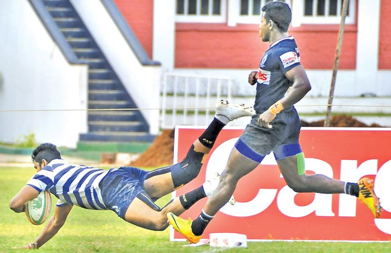 Navy's Thilina Weerasinghe goes over the line for a try in their Dialog 'A' division league rugby match against Police SC at Police Park yesterday. (Pic by Saman Mendis)