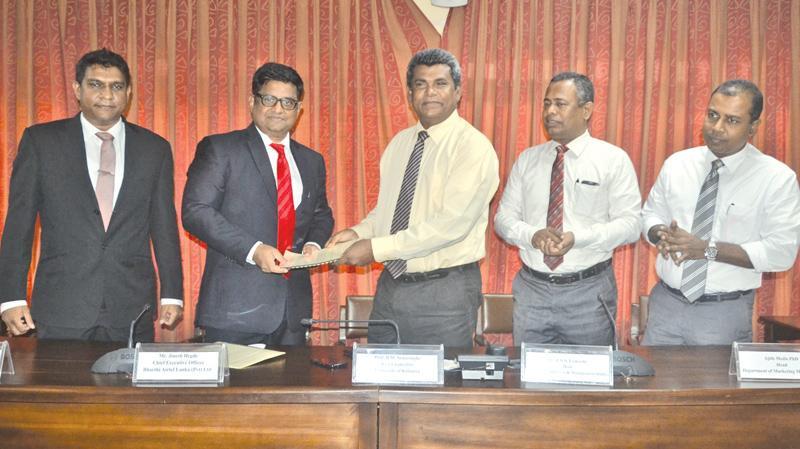 Airtel and Kelaniya University officials exchange the agreement.