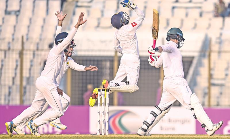 Sri Lanka wicket-keeper Niroshan Dickwella celebrates with his team mates the dismissal of Bangladesh opener Tamim Iqbal on the fourth day of the first cricket Test at the Zahur Ahmed Chowdhury Stadium in Chittagong on Saturday. AFP