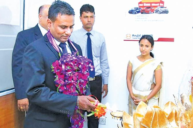 Chief Executive Officer, People's Merchant Finance PLC  Nishantha Gunasekara lighting the traditional oil lamp at the ceremonial relocation  of the Matara branch.