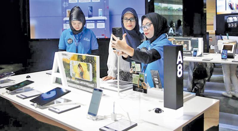 A salesperson shows a customer the latest smartphones in a showroom in Jakarta, Indonesia: the use of mobile internet services continues to grow rapidly in the country