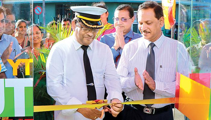 Chief Station Master K.S. Ananda Fernando opens the ATM.