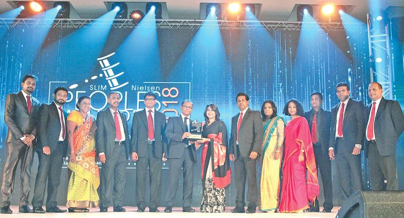 The Bank's General Manager/CEO Senarath Bandara receiving the 'Peoples Service Brand of the year' award (middle). The Bank's Chief Marketing Officer Dr. Indunil Liyanage, Deputy General Manager Sales and Channel Management C. Amarasinghe, Assistant General Manager Marketing Priyal Silva and officials of the Bank's Marketing and Business Development department are also present.