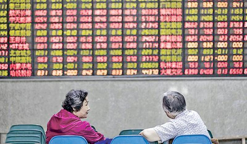 Investors sit in front of an electronic stock board at a securities brokerage in Shanghai, June 9, 2017. Pic: VCG