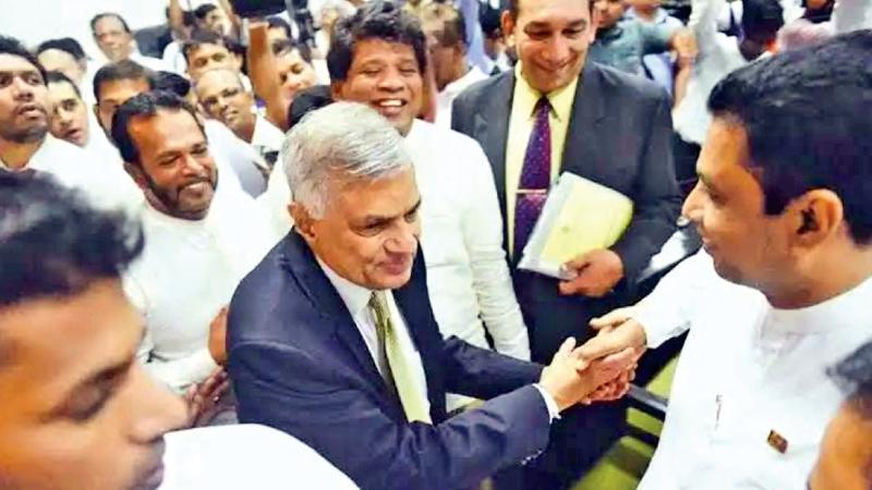 Prime Minister Ranil Wickremesinghe surrounded by supporters in the well of Parliament