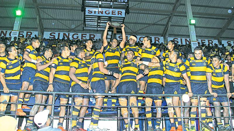 The Royal College team celebrate with the Bradby Shield after beating Trinity