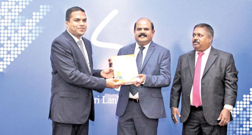 The first print copy of the SLT Rainbow Pages Directory 2018/19 being presented to Minister Harin Fernando by Chairman - Sri Lanka Telecom, Kumarasinghe Sirisena  and Chief Executive Officer - SLT Rainbow Pages, Malraj Balapitiya