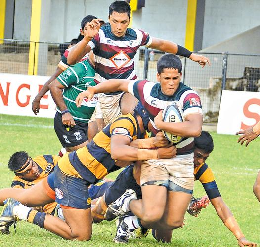 Zahira College player Shamin Nassar pushes through the grip of a tackle in his team's inter-school second round League rugby match against Royal College at the Royal Complex ground in Colombo yesterday. (Picture by Saman Mendis)