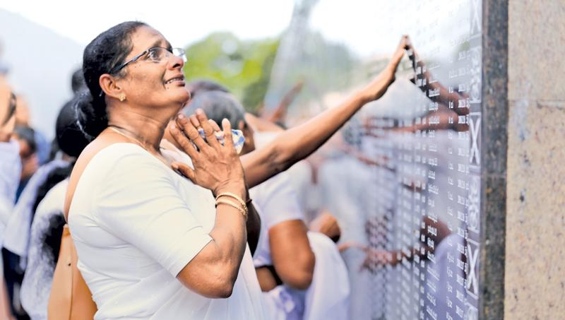 Tribute to Fallen Heroes: Overcome with emotion and memories, a mother of a fallen hero looks up her son's name among the names  inscribed at the Memorial.  (Pic: Chinthaka  Kumarasinghe)