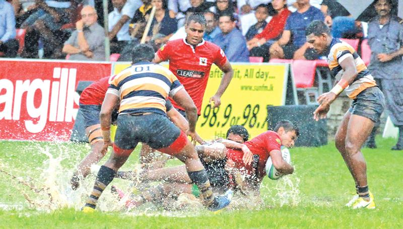 A Peterite forward brings down a Kingswood opponent in their muddy match at Havelock Park  Pic: Samantha Weerasiri