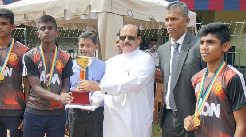 K Bandara the captain of the Under-16 boys champions Wickremabahu, receiving the Trophy from the Chief Minister Sarath Ekanayake as Director of Physical Education Athula Jayawardena looks on