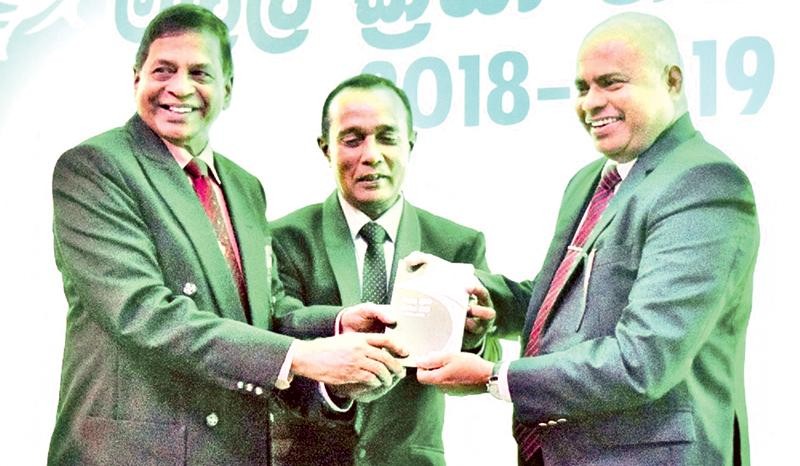 Sunil Hettirachchi(right) secretary Ministry of  Education receiving the copy of rule and regulation of track and field from Sunil Jayaweera.