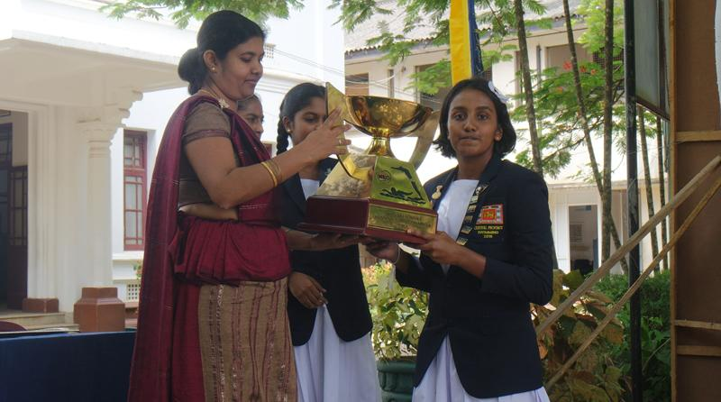 Maheshika Hewege the captain of the Mahamaya College swimming team receives the trophy from acting principal of the school Himali Senadheera