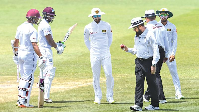 Umpire Aleem Dar inspects the ball in the presence of Sri Lanka captain Dinesh Chandimal at St. Lucia in the West Indies