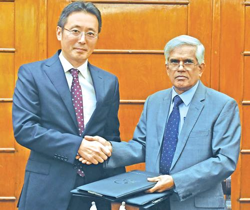 Secretary, Ministry of Finance and Mass Media, Dr. R.H.S. Samaratunga and Chief Representative of JICA Sri Lanka office Fusato Tanaka exchange copies of the agreement.