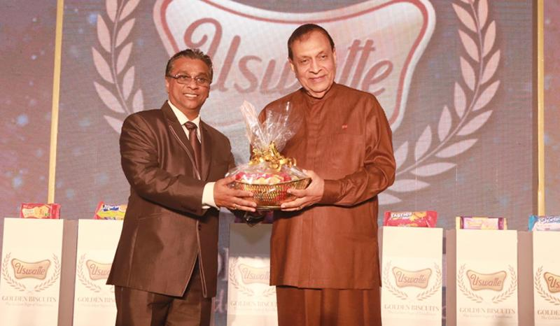 Uswatte Confectionery Works (Pvt) Ltd., Chairman and Managing Director Quintus Perera presents a sample of the new range of Uswatte Golden Biscuits to Speaker Karu Jayasuriya. Pic: Chaminda Niroshana