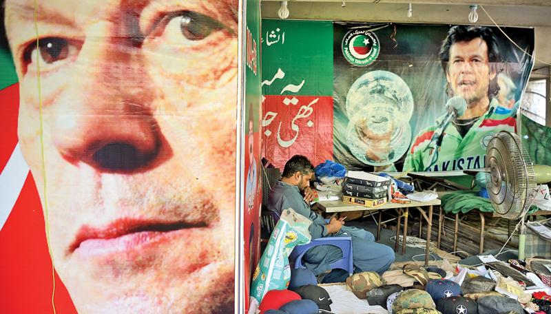 A vendor sits at his stall beside the posters of Pakistan's cricketer-turned politician Imran Khan                        (AFP)