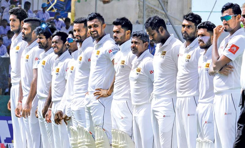 Sri Lankan cricketers stand to attention before the start of a match in this file photo taken by Saman Mendis