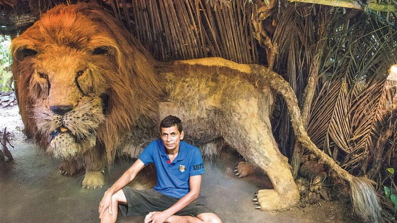 "PRIDE OF THE ZOO: Creator Dharmakumara Wettasinghe poses in front of his creation of the lion in the ""Sinha waadiya,"" model zoo"