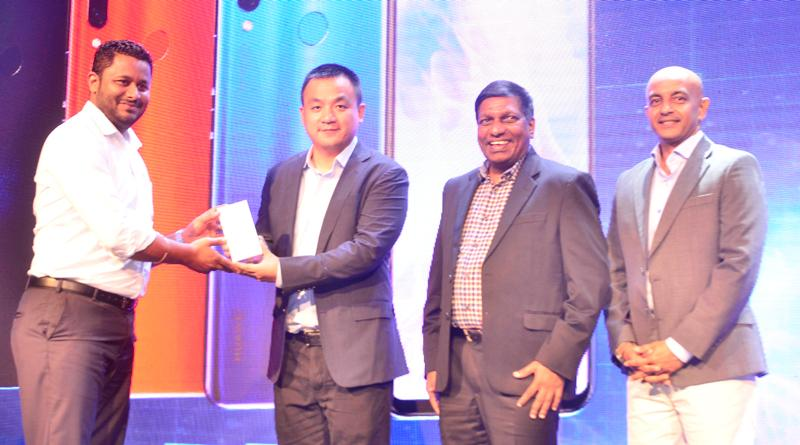 Huawei Device Sri Lanka Country Head Peter Liu hands over a phone to a customer at the launch. Picture by Chaminda Niroshana