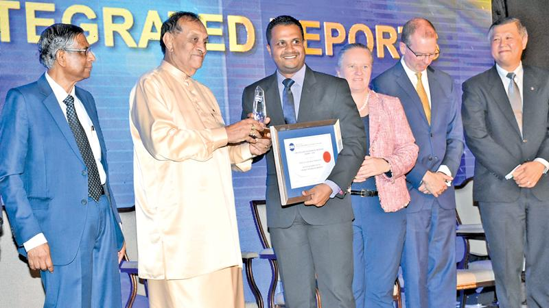 'Ten Best Integrated Reports' award being presented to PLC's Chief Manager - Finance, Omal Sumanasiri by the Speaker Karu Jayasuriya