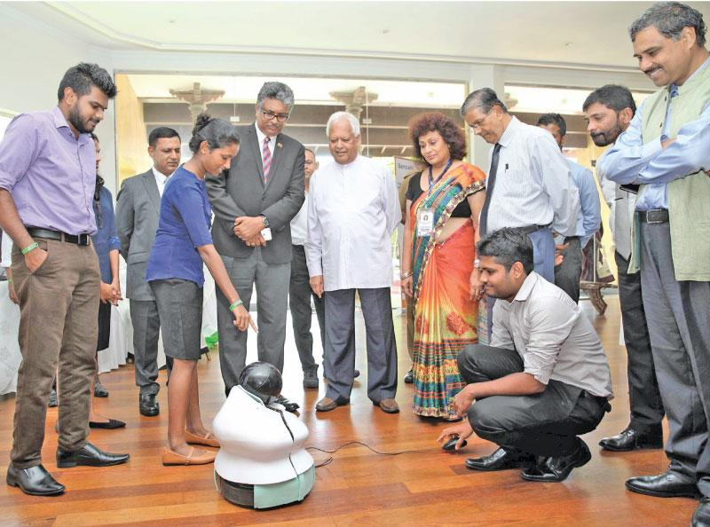 Minister Sarath Amunugama takes a close look at a robot on the sidelines of the conference.