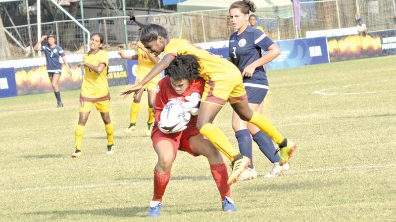 Sri Lanka's Senuri Bandara (in yellow) collides with Guam's goal-keeper Kiarra Annabella