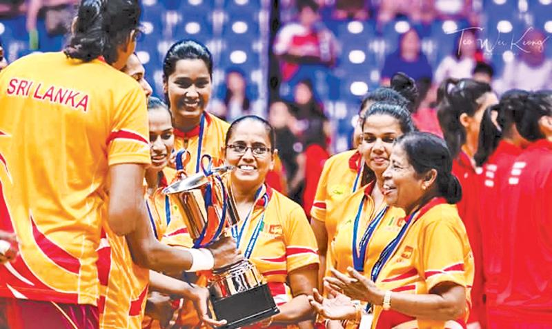 Thilaka Jinadasa is greeted by her jubilant players with the Asia Cup won in Singapore last week in the presence of Trixie Nanayakkara
