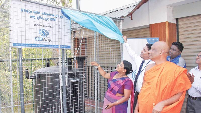 Chief Incumbent of Sri Abhinawarama Temple, Monaragala District Secretary Mrs. D. S. Padmakulasooriya and SDB bank's Head of Marketing and Retail Banking open the biogas unit.