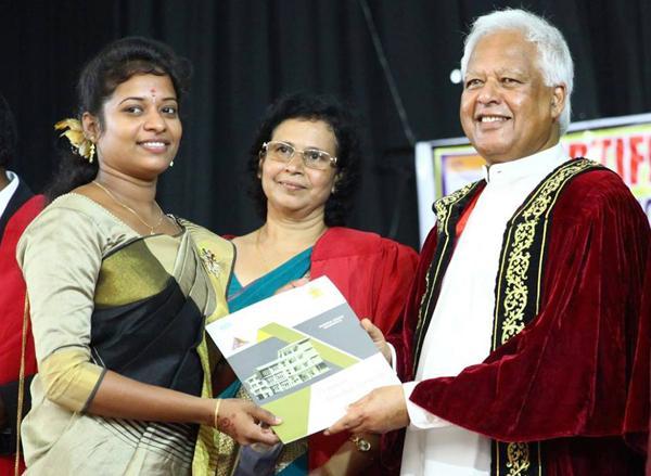 Minister Amunugama presents a certificate to a student.