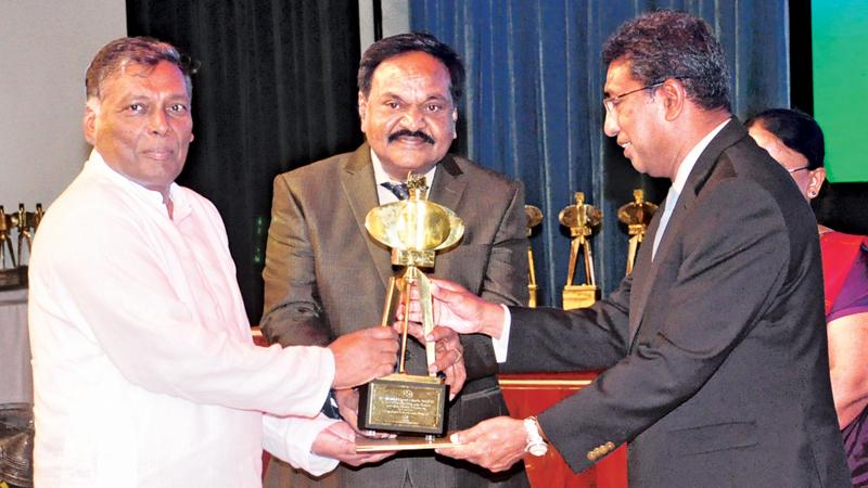 Chairman / Managing Director, Narayanasamy Gokulakrishnan receives the award from Minister Harsha de Silva. Director Sinnathamby Balasundaram looks on.