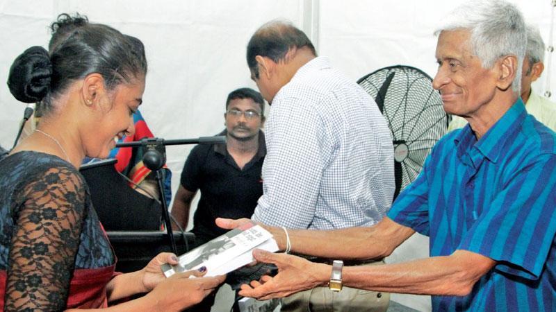 Presenting the first copy of the book to veteran journalist and former Sarasaviya and Silumina editor Thilakaratne Kuruwita Bandara