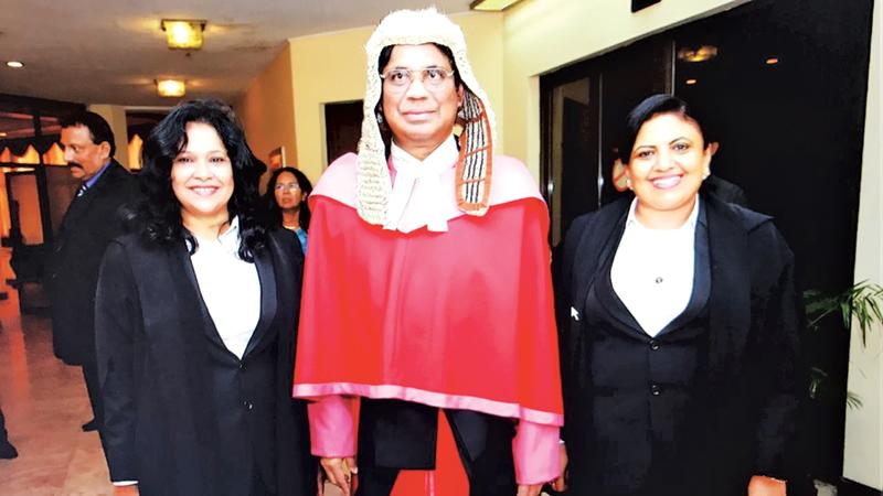 Members of the SLWLA sported the new lady lawyers' attire during the ceremonial farewell for the former CJ as an appreciation for approving the new attire. Seen here are the President and Secretary of SLWLA with the former CJ.